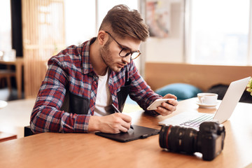 Freelancer man drawing on tablet at laptop sitting at desk.