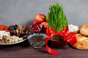 Traditional Azerbaijan holiday Nowruz: national dessert called Sumalak and Fresh green grass samani symbol of spring