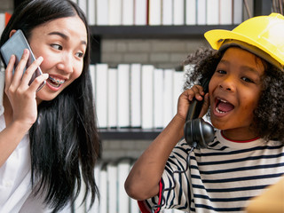 Young asian nanny playing telephone calling with cute curly hair boy after school