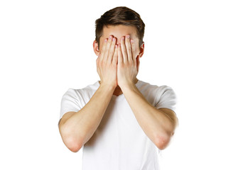 Man in white t-shirt covering his face with hands over white background