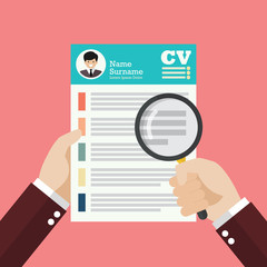 Hand holding magnifying glass over Curriculum Vitae