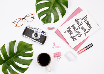 Woman workspace with handwritten quote notebook, vintage camera, coffee cup, lipstick, stationery and palm leaf. on white background. Flat lay, top view. summer stylish female blogger concept.