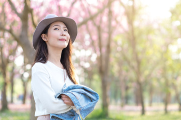 Young woman with smilling in cherry blossom garden in Spring day morning