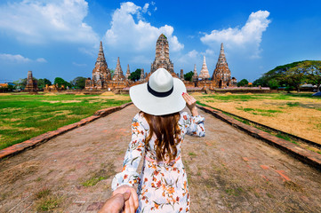 Wall Mural - Woman holding man's hand and leading him to Ayutthaya Historical Park, Wat Chaiwatthanaram Buddhist temple in Thailand.