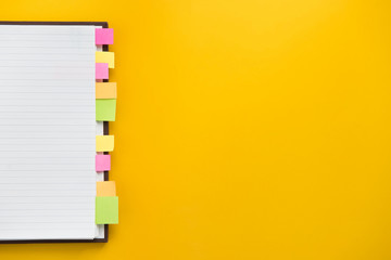 Open blank notebook with colorful sticky bookmarks on yellow paper background
