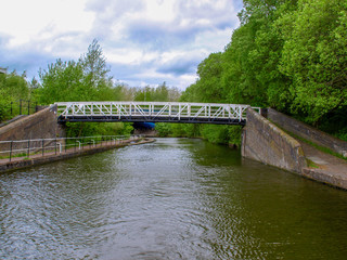 Black and white steel bridge over the Trent and Mersey Canal near Stoke-on-Trent in Staffordshire, England.