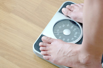 Image of woman feet standing on weigh.Health and weight loss
