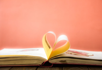 Heart shaped book pages. Old book page decorate to heart shape in vintage color tone. Composition of love with open book rolled in heart.
