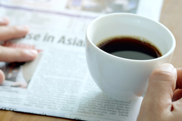 Man holding a cup of coffee in the background reading a newspaper.
