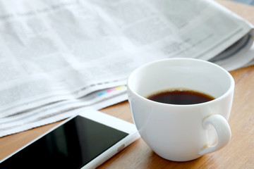 Coffee cup and smartphone on desk, newspaper background
