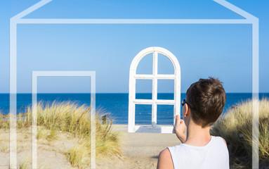 Wall Mural - Traumhaus am Strand - Junge blickt durch ein Fenster auf das Meer