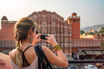 Young woman takes picture of Hawa Mahal in India