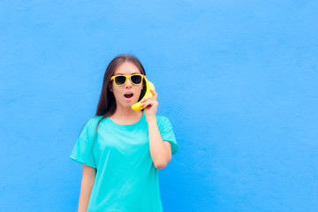 Funny Girl with Sunglasses and Banana Phone on Blue Background