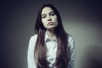 Portrait of a young adult woman in a white shirt thoughtful