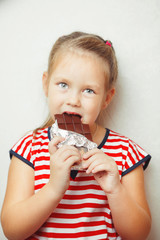Lady of young age eating chocolate wrapped in tinfoil