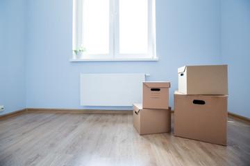 Cardboard boxes on laminate floor in empty room