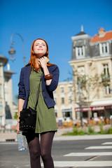 woman in styling dress walking on Parisian streets