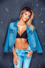 Confident blonde in jeans and stylish bra holding denim jacket on shoulder looking alluringly at camera.