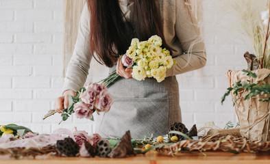 woman florist collects bouquet decorates different flowers