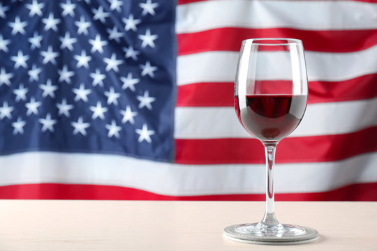 Glass of wine on table against American flag background