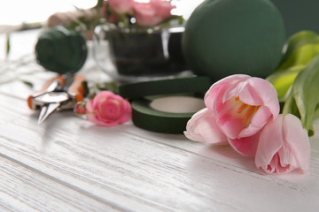 Florist equipment with flowers on wooden table