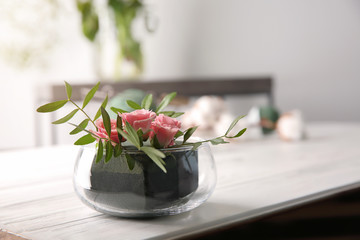 Glass bowl with flowers in sponge on table