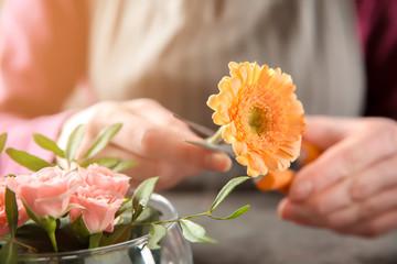 Female florist making beautiful bouquet at table, closeup