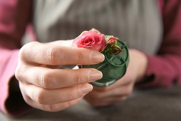 Female florist using sponge for work at table, closeup