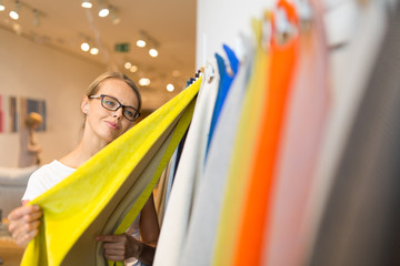 Pretty young woman  choosing the right material/color for her modern appartement interior (shallow DOF; color toned image)