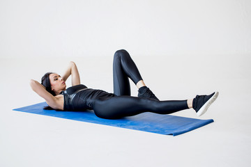 Close-up view of the sports charming woman lying on the mat and doing bicycle crunches in the white studio.