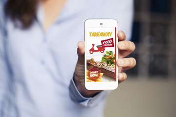 Food delivery take away app in a mobile phone screen. Woman holding phone in the hand.