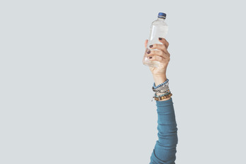 Woman holding water bottle raised up arm