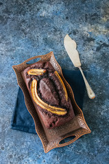 Chocolate banana date dread on a vintage tray on a blue stone background. Copy space.