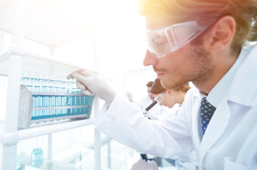 side view of focused scientist holding test tube in laboratory
