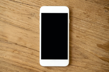 Mockup image of white mobile phone with blank black screen on vintage wooden table background