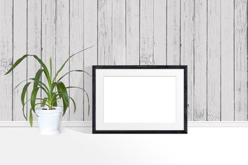 Photo frame mockup and yucca plant in flower pot near wooden planks wall