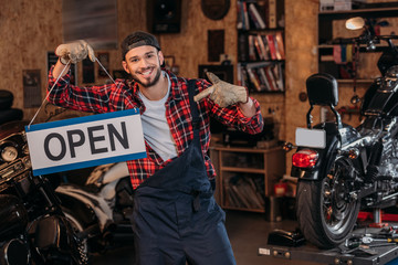 happy bike repair station worker pointing at open signboard at garage