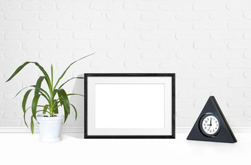 Photo frame mockup, yucca plant in flower pot, table clock near white bricks wall