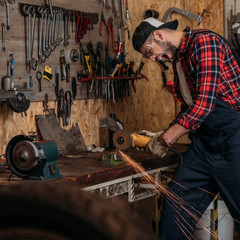 screaming bike repair station worker using electric circular saw at garage