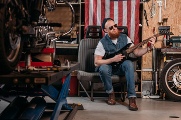 bearded man playing electric guitar at garage with usa flag hanging on wall