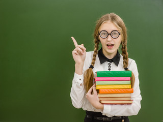 Smiling nerd student girl  with books on the background of a school board pointing away. Space for text