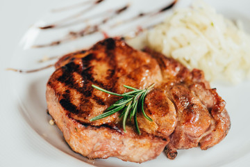 close-up view of fresh delicious grilled steak with rosemary on plate