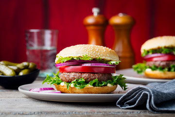 Burger on a plate. Wooden background. Copy space.
