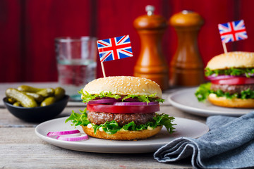Burger with British flag on top. Wooden background. Copy space.