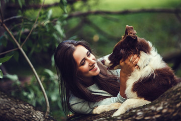 Beauty smiling woman with her dog playing outdoors