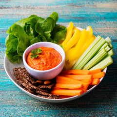 Assorted fresh vegetables with dip. Healthy eating. Roasted pepper sauce, spread. Wooden background.