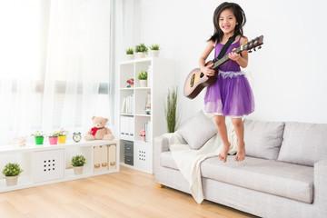 Female kid jump on the sofa.