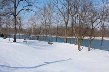 A view of the snowy park landscape on a sunny cold day.