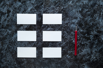 few clean white business cards with space for text and a red fountain pen on a dark marble surface