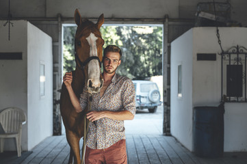 Portrait of man with horse in stable